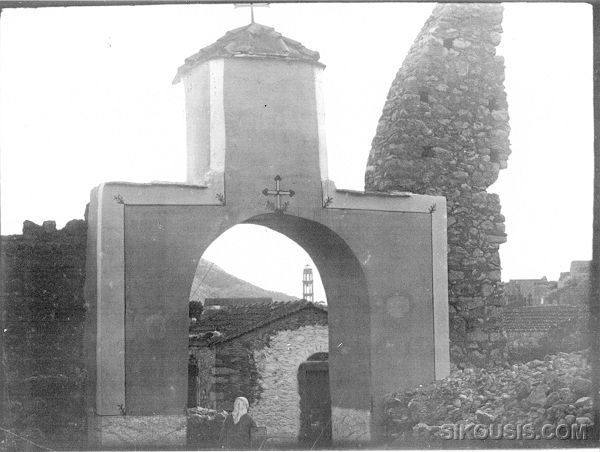 The old entrance to the Agios Georgios Monastery &quot;Stavros&quot;. In the background the Agios Panteleimon bell tower can be seen as well as part of the monastery exterior wall that was destroyed during the 1881 earthquake. A 1928 picture by Perikles Papahatzidakis.<br>From the Archives of Vaggelis Roufakis.
